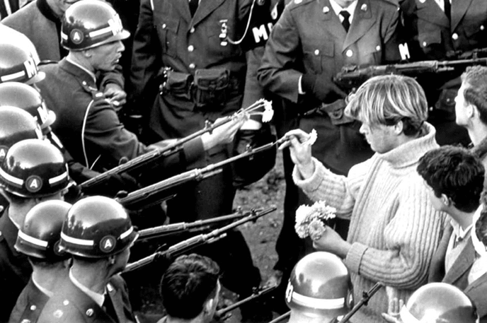 Un homme met des fleurs dans les canons des fusils des soldats